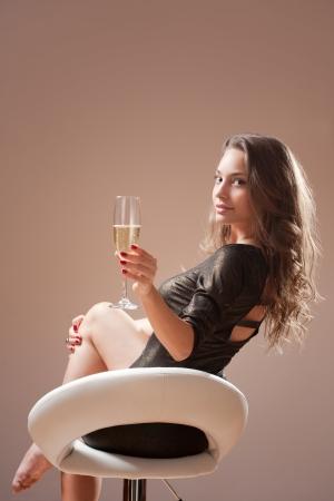 Portrait von festlichen Brünette Schönheit auf Barhocker mit einem Glas Champagner. Standard-Bild - 20680057