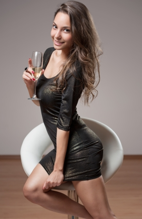 Portrait of festive brunette beauty on barstool with glass of champagne.