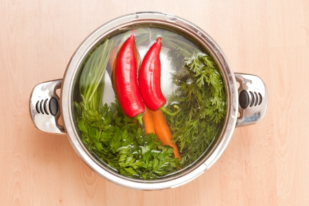 cooking pot: Shot of shiny metal pot filled with water and soup ingredients. Stock Photo
