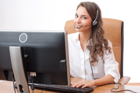 latinos: Beautiful young brunette woman in offfice wearing headset.