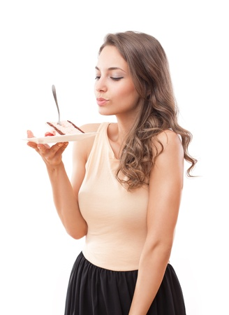 woman eating cake: Fit beautiful young brunette woman tempting you with cake. Stock Photo