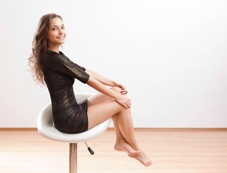 pies sexis: Esbelta joven belleza descalza que presenta en taburete de la barra blanca