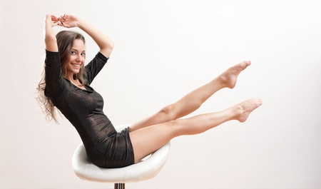 tight dress: Gorgeous young brunette woman balancing on barstool with extended legs  Stock Photo