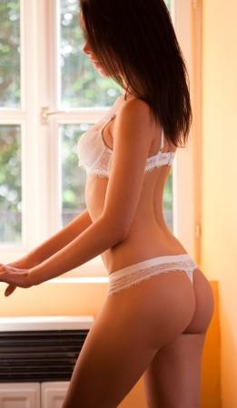 thongs: Relaxing shot of young slender brunette lingerie model.