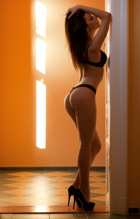 thong woman: Very sensual slender young brunette model in black lingerie.