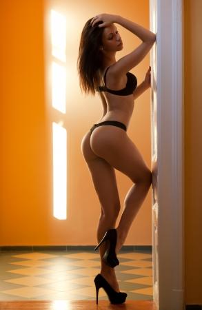 thong panties: Very sensual slender young brunette model in black lingerie.