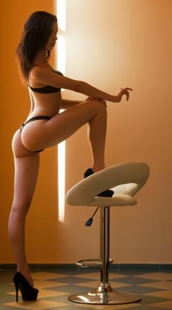 butt: Very sensual slender young brunette model in black lingerie.