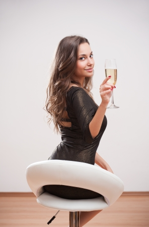 Portrait of festive young brunette holding glass of champagne. photo