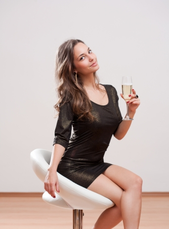 barstool: Portrait of cute festive young brunette champagne girl. Stock Photo