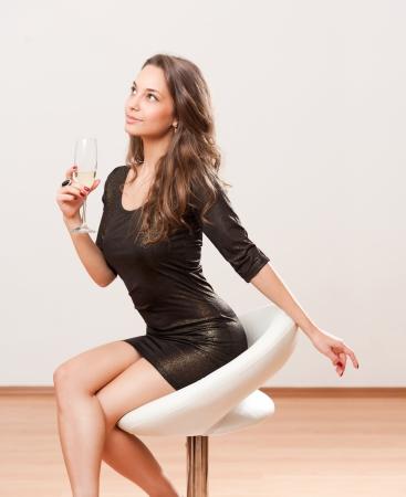 slender: Portrait of a beautiful festive champagne brunette on a bar stool. Stock Photo