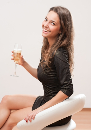 Portrait of a cool attractive  festive young woman sitting in white bar stool. photo