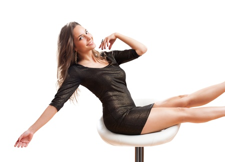 Portrait of very happy young brunette beauty balancing on a bar stool. photo
