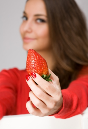 Portrait of gorgeous young brunette with fresh ripe strawberries. photo