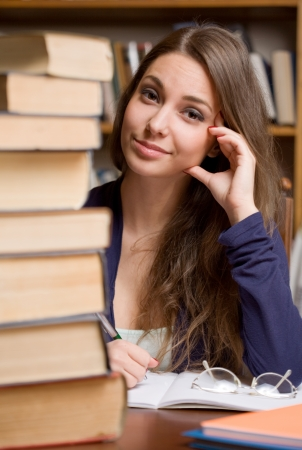 examination stress: Portrait of a worried looking young brunette student girl with pile of books.