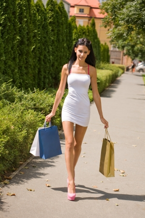 Portrait of gorgeous brunette shopper walking on the street with colorful shopping bags. photo