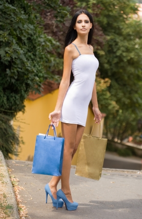 to tight: Gorgeous young brunette shopping girl on the street in sunshine. Stock Photo