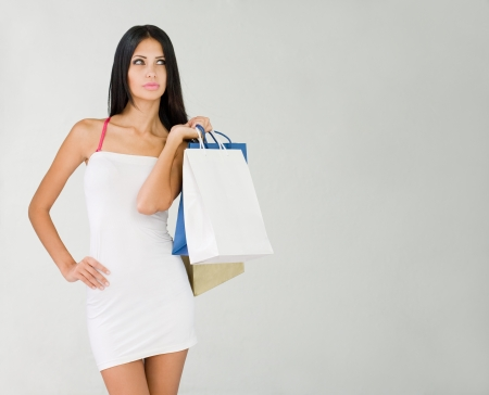 Beautiful slender young brunette woman with colorful shopping bags. photo