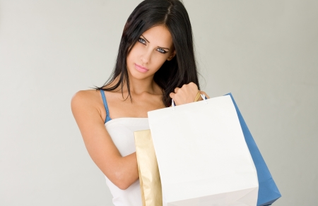 Sensual young brunette woman holding colorful shopping bags. photo