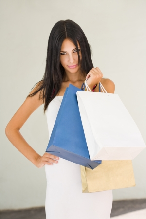 Portrait of a beautiful brunette shopper in tight white dress. photo