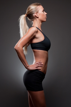 Portrait of very fit young slender woman on dark gray background. photo
