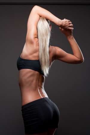 Portrait of proud young blond woman showing off slender fit body. photo