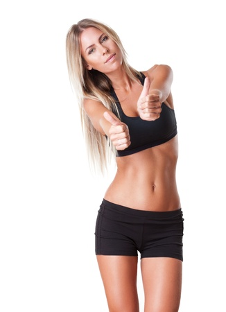 Very fit young blonde beauty showing thumbs up. photo