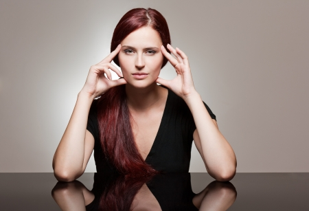Portrait of a redhead beauty with strong facial expression. photo