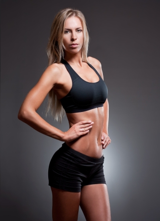 Slim and muscular tanned young fitness woman. photo