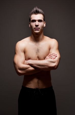 Dark moody portrait of very fit ripped young athlete. photo