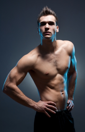 shirtless male: Dark moody portrait of very fit ripped young athlete.