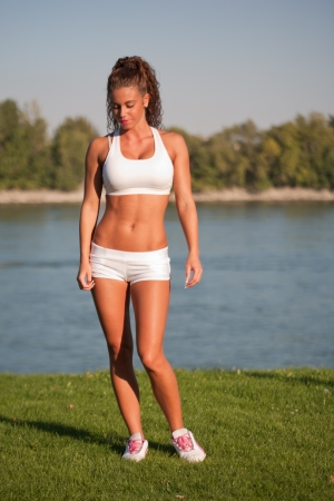 Gorgeous very fit young brunette having great workout outdoors. photo