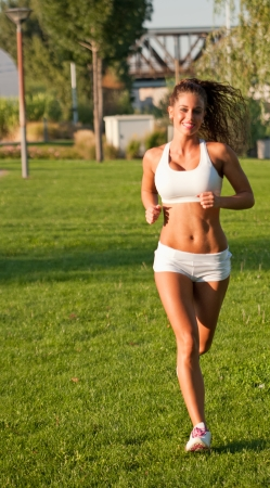 Portrait of gorgeous sporty young brunette having fitness fun outdoors. photo