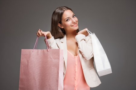 Portrait of a brunette beauty with pink and white shopping bags. Stock Photo