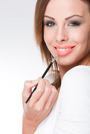 lip shine: Ritratto di bruna bellezza trucco applicando lucentezza del labbro Archivio Fotografico