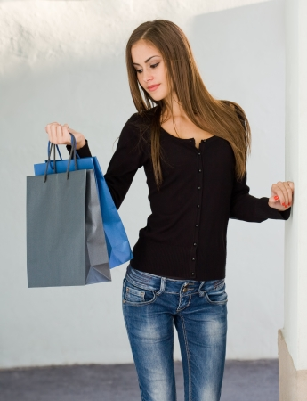 skinny woman: Portrait of a gorgeous young shopper girl holding colorful shopping bag.