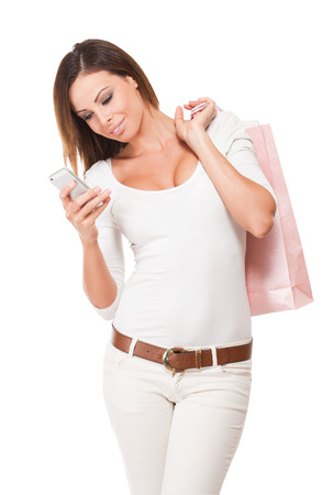 Portrait of beautiful fashionable young shopper using smartphone. photo