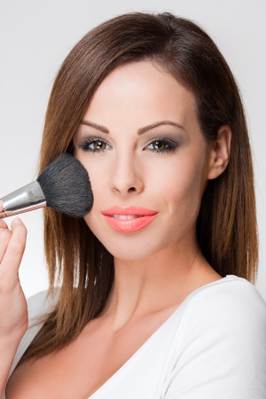 Gorgeous young brunette woman using makeup tools. photo