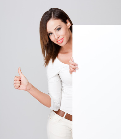Portrait of a fashionable brunette beauty with blank white billboard for text. photo