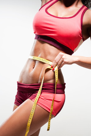 Beautiful young fitness woman showing of perfect abs with measuring tape. photo