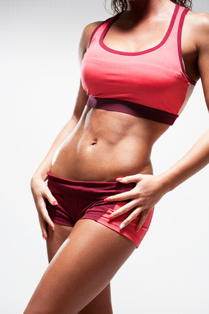 Super fit young woman showing off her perfect muscular abs. photo