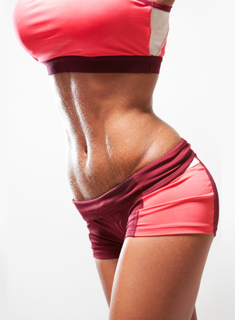 six persons: Super fit young woman showing off her perfect muscular abs. Stock Photo