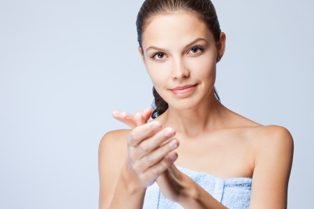 Portrait of a young brunette beauty using lotion. Stock Photo - 23175064