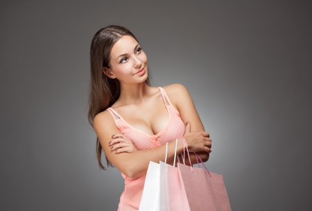 Portrait of a young brunette beauty with shopping bags. photo