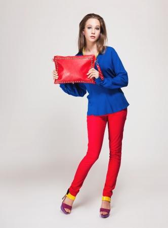 tacones rojos: Retrato de una joven y bella modelo posando en ropa elegante.