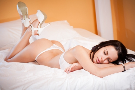 Portrait of a slim sexy lingerie woman in bed with white sheets.  photo