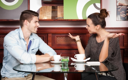 Portrait of a young couple having fun and conversation in a coffee shop. photo
