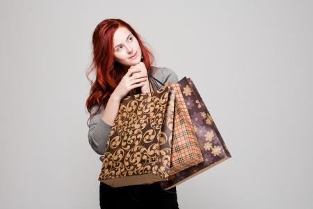 Portrait of a beautiful young redhead woman holding colorful shopping bags. photo