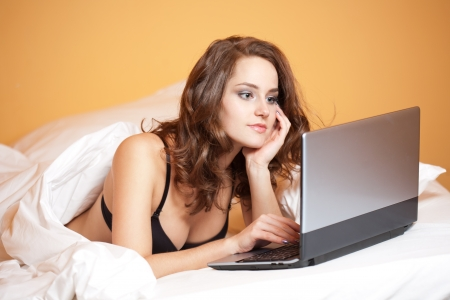 Portrait of a sensual young woman using laptop in bed. photo