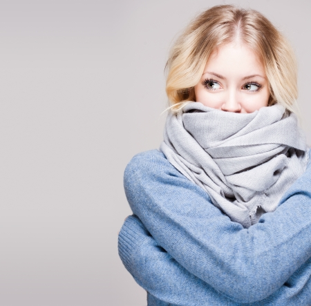 Portrait of blond winter beauty in light blue swater and scarf.