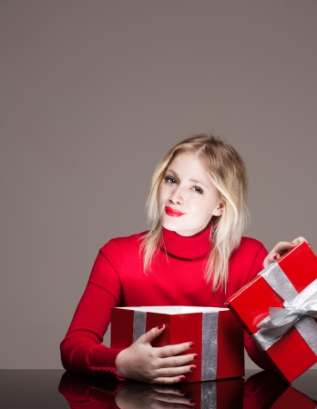 Portrait of a cute young blond with bright red gift box. photo